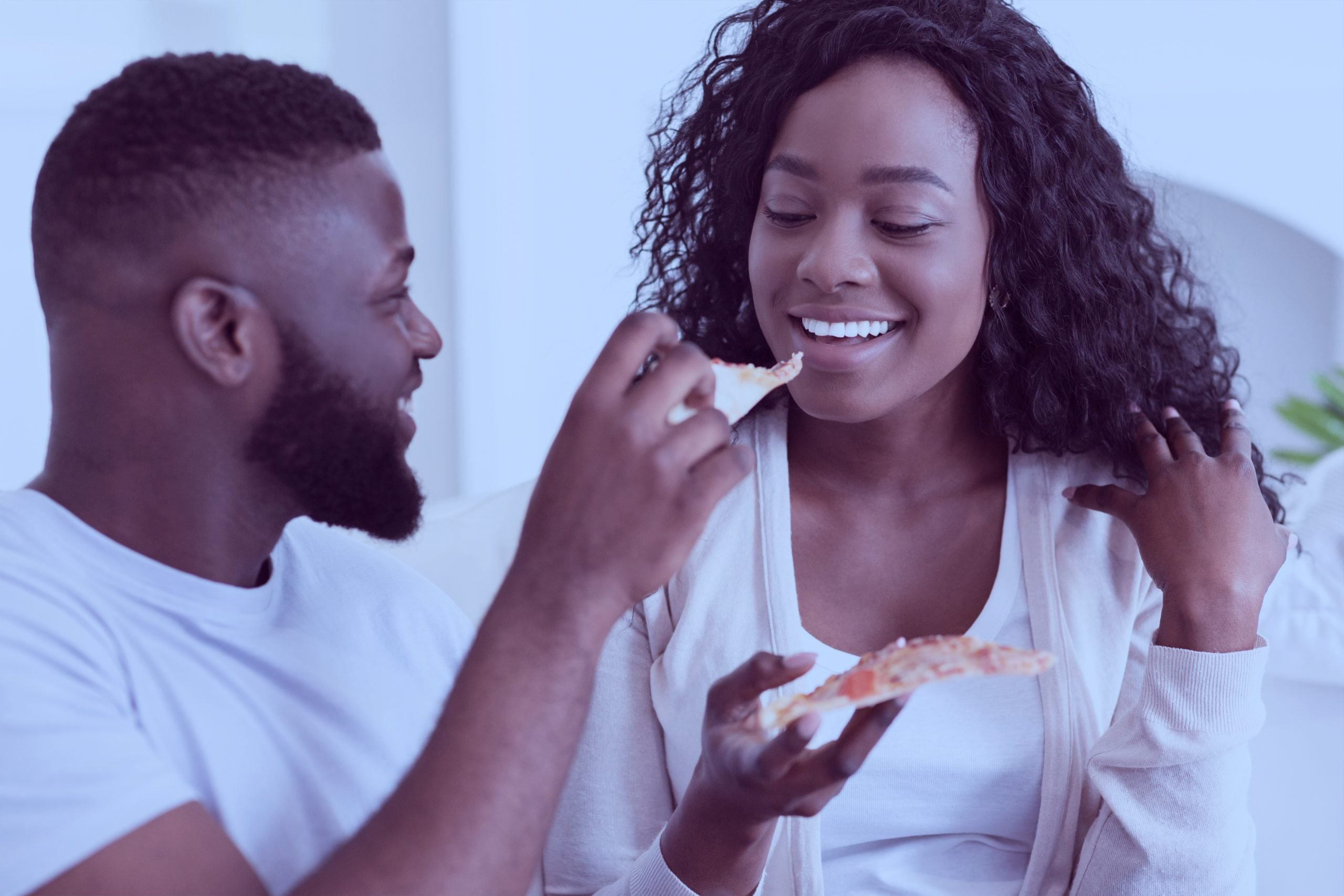 young-black-couple-sharing-pizza-on-date-at-home-C89KNF7